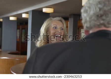 Mature Woman Laughing in Theater Bar