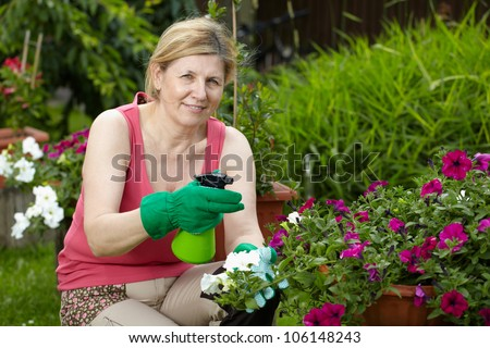 Mature woman look after her garden, spray water over flowers using green bottle