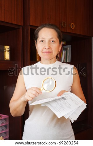 mature woman looking at utility bills through  magnifier