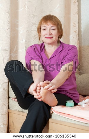 Mature woman looks at her toenails