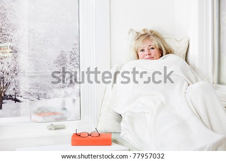 Mature woman lying down & smiling from under a warm blanket