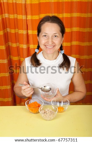Mature woman making cosmetic pack from carrot, oatmeal and egg yolk