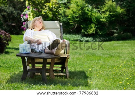Mature woman napping in a garden chair