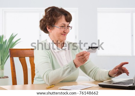 mature woman online banking, holding credit card