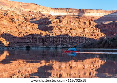 Mature woman paddling glass calm Green River in Stillwater Canyon