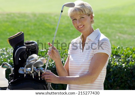 Mature woman playing golf, taking golf club from bag, smiling, side view, portrait