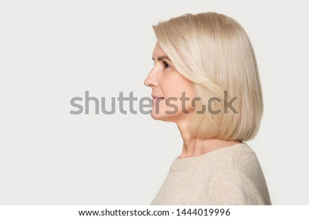 Mature woman profile view studio portrait isolated on gray background. Blond female with good styling, hairstyle side view headshot. Old lady looking to left, copyspace mockup template, blank space