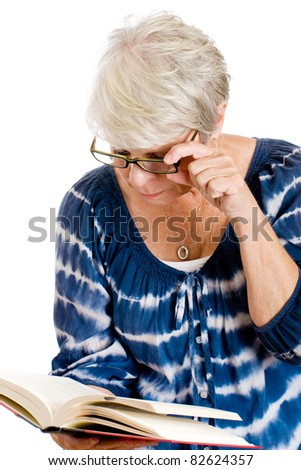 Mature woman reading a book with the help of glasses for her vision.