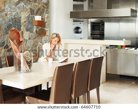 stock photo : Mature woman reading book in dining room by kitchen in a ...