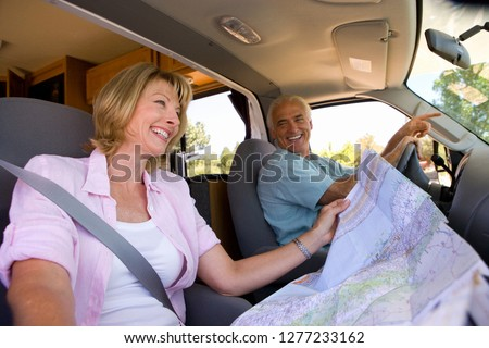 Mature woman reading map in motor home with husband driving