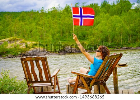Mature woman relaxing outdoor, holding norwegian flag, sitting on wooden chair on lake fjord shore. Holidays relaxation and trip. Norway Scandinavia Europe.