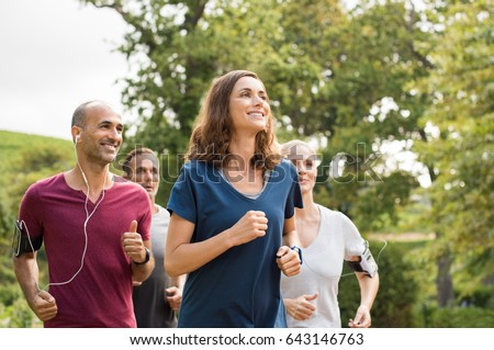 Shutterstock Mature woman running with group of people at park. Happy smiling woman with group of friends running together. Senior runners team on morning training.