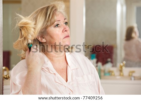 Mature woman's morning routine - absentmindedly brushing her hair