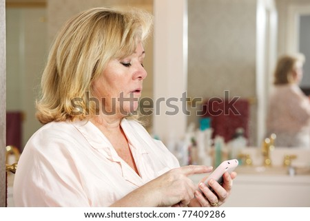 Mature woman's morning routine - checking e-mail before anything else - stock photo