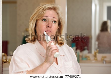 Mature woman's morning routine - cleaning her teeth