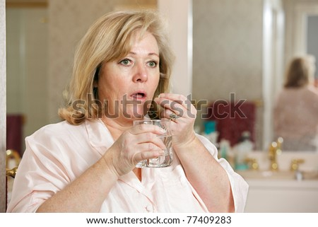 Mature woman's morning routine - taking medicine with glass of  water