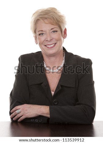 mature woman sitting behind desk on white background #113539912