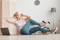 Mature woman sitting on exercise mat and doing exercises she watching sports training online on laptop while sitting at home