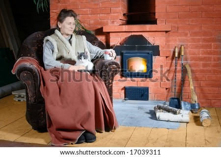 Mature woman sitting with three cats in armchair near stove in country house