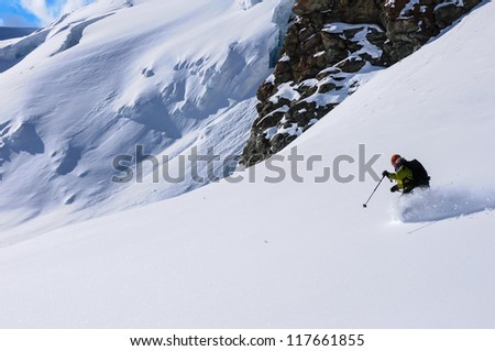 Mature woman skiing powder snow on a glacier in the Val de Ayas, Italian alps.