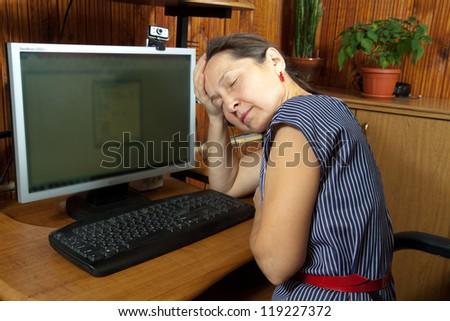 Mature woman  sleeping; at  computer at home