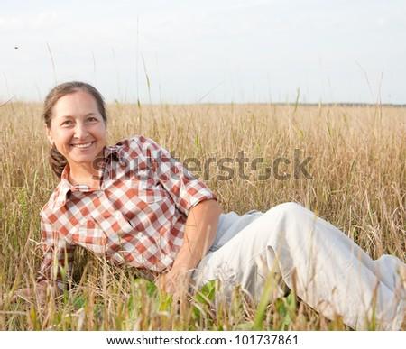 Mature woman  smiling against summer landscape
