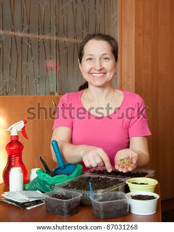 Mature woman sows sprouts at her  home