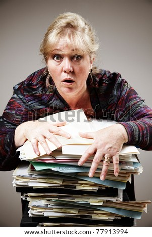 Mature woman struggles to control huge stack of paperwork