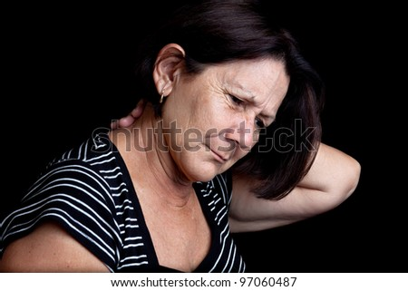 Mature woman suffering from neck or shoulder pain on a black background with space for text