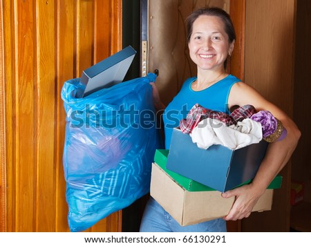 Mature woman taking away the garbage at home