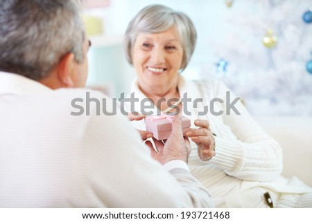Mature woman taking small pink giftbox from her husband hands