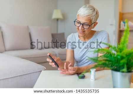 Mature Woman testing for high blood sugar. Woman holding device for measuring blood sugar. Woman doing blood sugar test. Woman checking blood sugar level by glucometer and test stripe at home