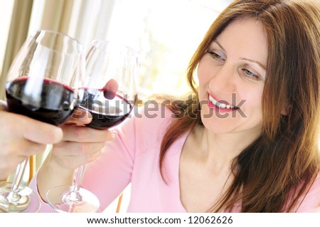 Mature woman toasting with a glass of red wine