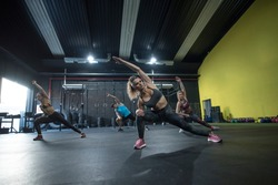 Mature woman training crossfit class and strenght flexibility exercises at gym floor