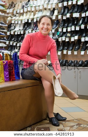 Mature woman trying shoes  for size  at shoes shop