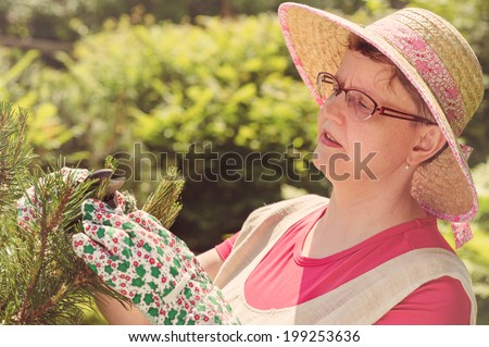 Mature woman use pruning scissors in the garden, cross processed image