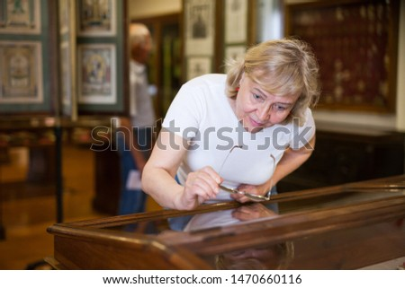Mature woman visiting exposition of Art Museum with exhibits of antiquity