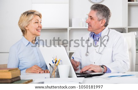Mature woman visits doctor for survey of condition of health #1050181997