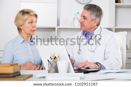 Mature woman visits doctor in hospital for survey and check of your health #1102951187