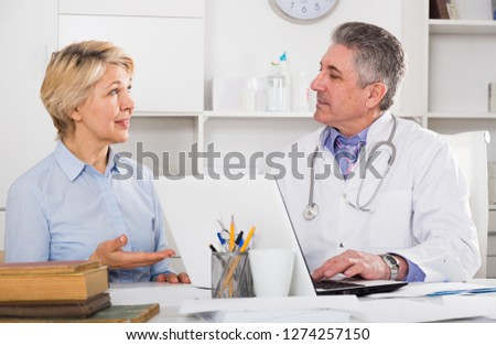 Mature woman visits doctor in hospital for survey and check of your health #1274257150