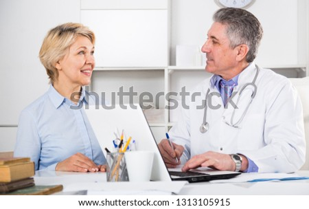 Mature woman visits doctor in hospital for survey and check of your health #1313105915