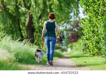 mature woman walking with Brittany dog at the leash on a country path