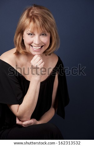 mature woman wearing black outfit on dark blue background