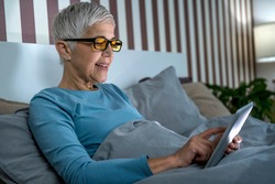 Mature woman wearing blue light blocking glasses with amber lenses, lying in bed before sleep, looking at tablet screen