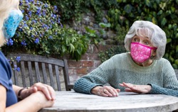 Mature Woman Wearing Mask Visiting Lonely Senior Mother In Garden During Lockdown