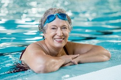 Mature woman wearing swim goggles at swimming pool. Fit active senior woman enjoying retirement  in swimming pool and looking at camera. Happy senior healthy old woman enjoying active lifestyle.