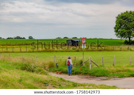 Mature woman with a backpack and her dog looking at the prohibition signs, prohibiting cars and motorcycles from passing on a dirt road with fences between farmland, South Limburg, Netherlands Сток-фото ©