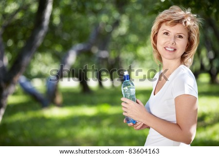 Mature woman with a bottle of water in the park