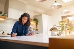 Mature Woman With Digital Tablet Reviewing Domestic Finances And Paperwork In Kitchen At Home