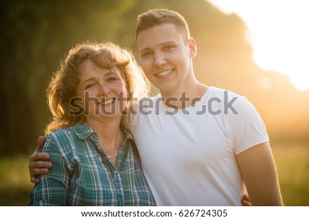 Mature woman with her adult son. Side hug. Family bond concept.